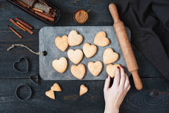 Female hand holding the baked cookies-hearts. On the vintage wooden table Stock Photos