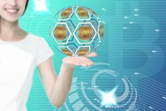 Female hand holding bitcoin icons. With beautiful smiling woman on background royalty free stock photo