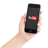 Female hand holding black Apple iPhone 5s with YouTube app logo. Female hand holding Apple iPhone 5S with YouTube app on the display. YouTube is a video-sharing Stock Photos