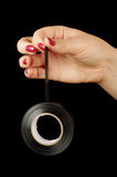 Female hand holding black gaffer tape roll Royalty Free Stock Image