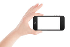 Female hand holding black smart phone in landscape orientation. Female hand holding black modern smart phone with blank screen in landscape orientation. Isolated Royalty Free Stock Photo