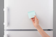 Female hand holding blank blue sticky paper note on refrigerator Stock Photography
