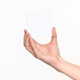 Female hand holding blank paper for records on white. Royalty Free Stock Photography