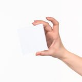 Female hand holding blank paper for records on white. Royalty Free Stock Photo