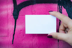 Female hand holding blank white business card over colorful back Stock Photo