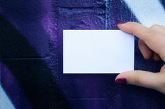Female hand holding blank white business card over colorful back Royalty Free Stock Images