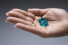 Female Hand Holding Blue Capsules Stock Photo