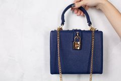 Female hand holding blue leather purse with golden chain. Space stock photo