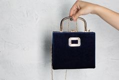 Female hand holding blue leather handbag with golden chain over royalty free stock image