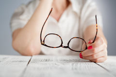 Female hand holding a brown framed glasses Stock Images