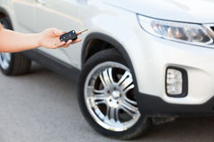 Female hand holding car key with suv on background Royalty Free Stock Photography