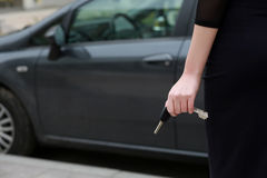 Female hand holding car keys. Back view. Female driver standing in front car, outdoors royalty free stock image