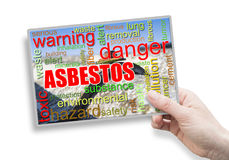 A female hand holding an card with asbestos theme Stock Images