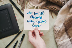 Female hand holding card with handwritten inspirational quote do small things with great love Royalty Free Stock Photos
