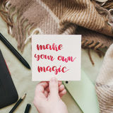Female hand holding card with handwritten inspirational quote `make your own magic`. Flat lay of artist home office in bed. Female hand holding card with Stock Images