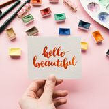 Female hand holding card with inspirational quote. Hello beautiful written in calligraphy style. Artist workspace on a pale pink pastel background Royalty Free Stock Photo