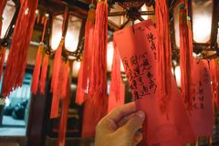 Hand holding a card with prayers hanging from a lantern in the Man Mo Temple in Hong Kong royalty free stock images