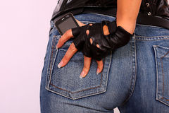 Female hand holding a cell phone in back pocket Stock Photo