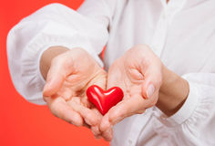 Female hand holding a ceramic heart. On red background royalty free stock photos