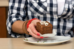 Female hand holding a chocolate cake. Close Up Royalty Free Stock Photography