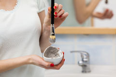 Female hand holding clay mud mask and brush. Skin care. Royalty Free Stock Photos
