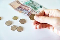 Female hand holding a coin, coins and russian rubles on the table stock photo