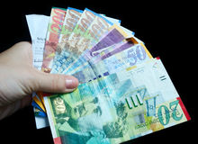 A female hand holding colorful shekel banknotes Stock Photography