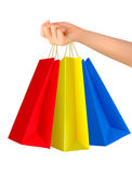Female hand holding colorful shopping bags. Stock Photos