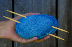 Female hand holding a cotton yarn ball with knitting needles Royalty Free Stock Images