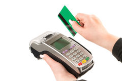 Female hand holding a credit card through the terminal. Woman's hand holding credit card terminal on a green on a white background, isolated Stock Photos