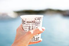 A female hand is holding a cup of coffee in front of sea and blurred view. A female hand is holding a cup of coffee in front of sea and beautiful view Stock Images