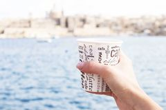 A female hand is holding a cup of coffee in front of sea and beautiful view on Valletta. Malta Royalty Free Stock Photos