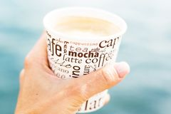 A female hand is holding a cup of coffee in front of sea and blurred view. A female hand is holding a cup of coffee in front of sea and beautiful view Stock Photos