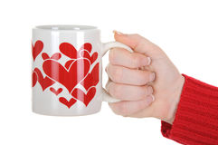Female Hand Holding a Cup With Red Hearts Royalty Free Stock Image