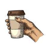 Female hand holding a disposable cup of coffee with cardboard holder and cap. Stock Photo