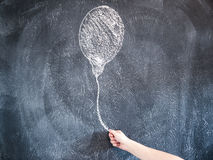 Female Hand holding a Drawn Balloon on a chalkboard stock image