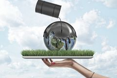 Female hand holding earth globe covered with black thick liquid from black oil barrel on green grass model on blue sky. Background. Ecology and environment stock illustration