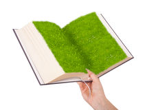 Female hand holding a ecological book with grass on white background Stock Image