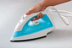 Female hand holding electric steam iron Royalty Free Stock Image