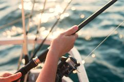 Female hand holding a fishing pole against the background of the sea. The woman is fishing stock photos