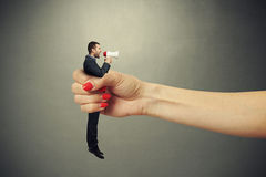 Female hand holding in fist small man Royalty Free Stock Image