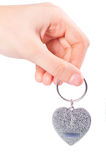 Female hand holding fob in the shape of heart Stock Photo
