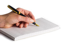 Female hand holding a fountain-pen over notepad Stock Photo