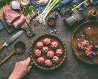 Female hand holding frying pan with meat balls on kitchen table with ingredients and tools Royalty Free Stock Image