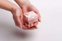 Female hand holding a gift with a bow. White background Royalty Free Stock Photo