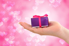 Female hand holding gift on pink heart background Stock Photo