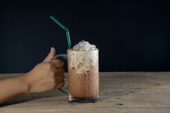 Female hand holding glass of ice coffee Royalty Free Stock Images