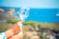 Female hand holding a glass with wine  on sea background Stock Photos
