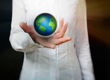 Female hand holding globe over black background Stock Images