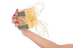Female hand holding gold and yellow gift box with a bow Stock Images